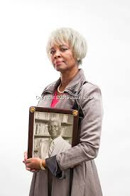 "Anna Jones, Filmmaker posing with portrait of her dad, James Jones"", an unsung share chopper who became a North Carolina's version of Martin Luther King!"